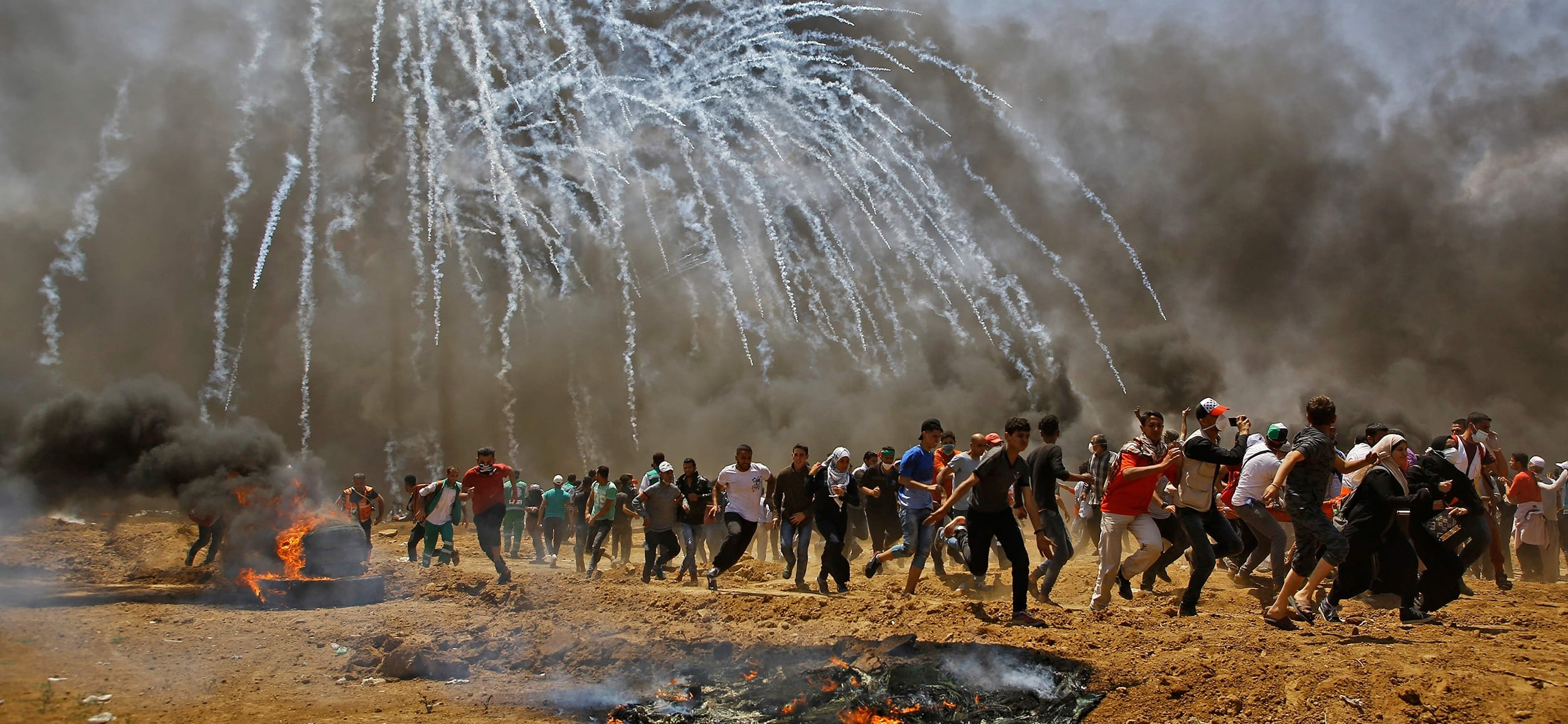 Palestinians run for cover from Israeli tear gas